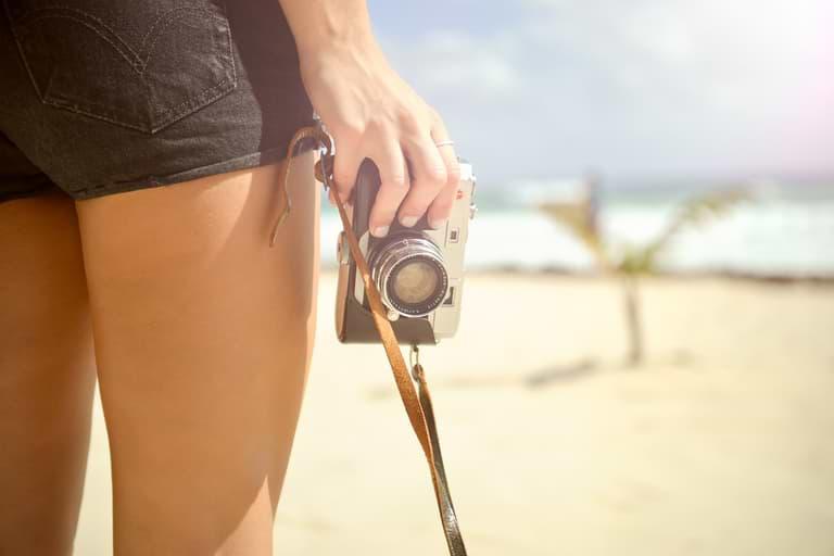 Frau hält Kamera glatte Beine Epilierer